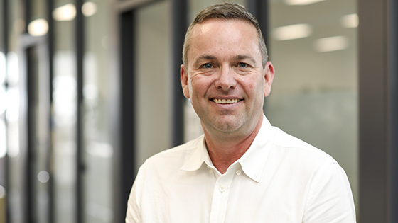 Picture of Grant Barnes, NRAR'sChief Regulatory Officer, smiling in a white-collared shirt in an office setting.