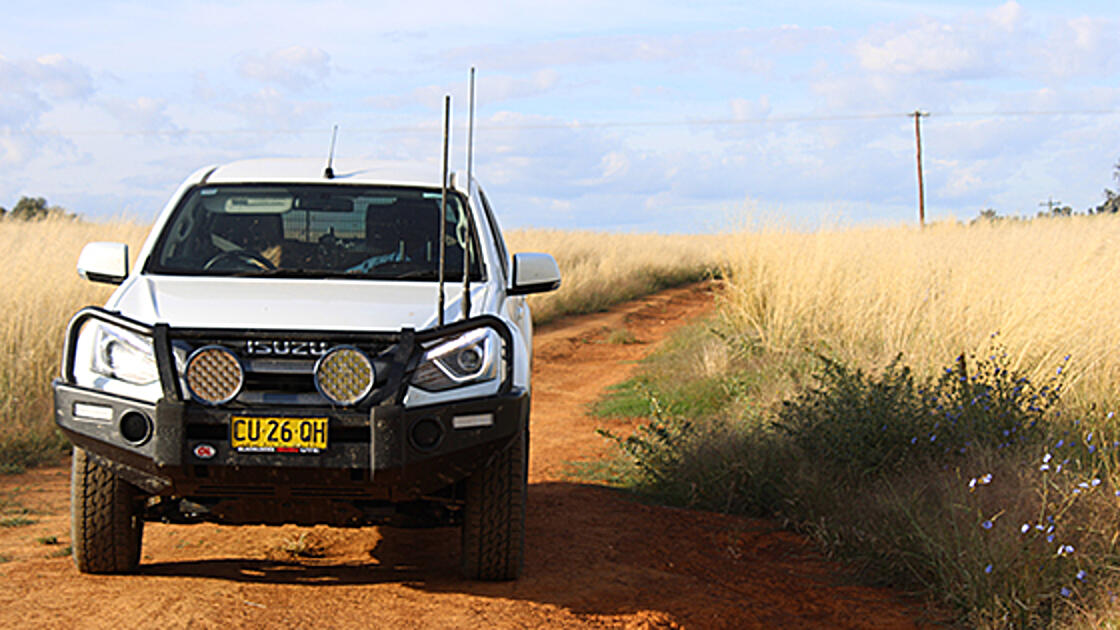 NRAR off road vehicle on a dirt road in a rural setting.