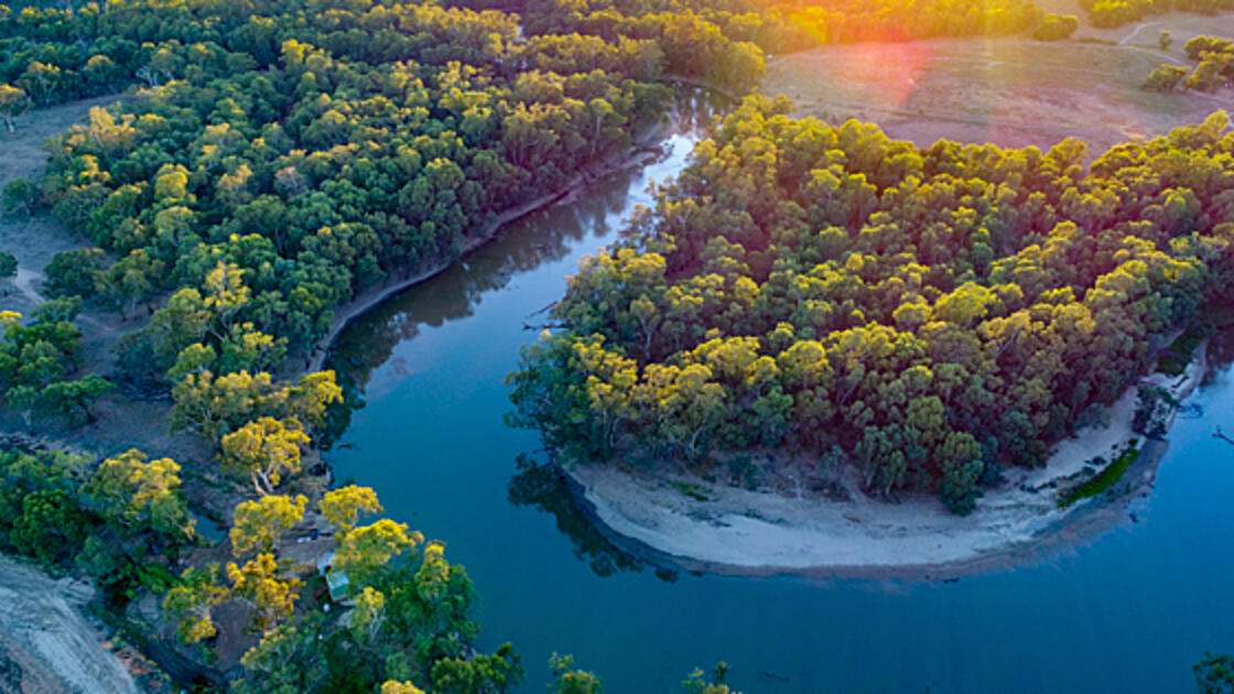 Aerial image of a winding river lined with green trees at sunset.