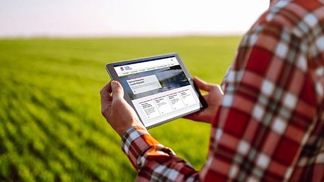 A person standing in a field holding a tablet to view the NRAR website.
