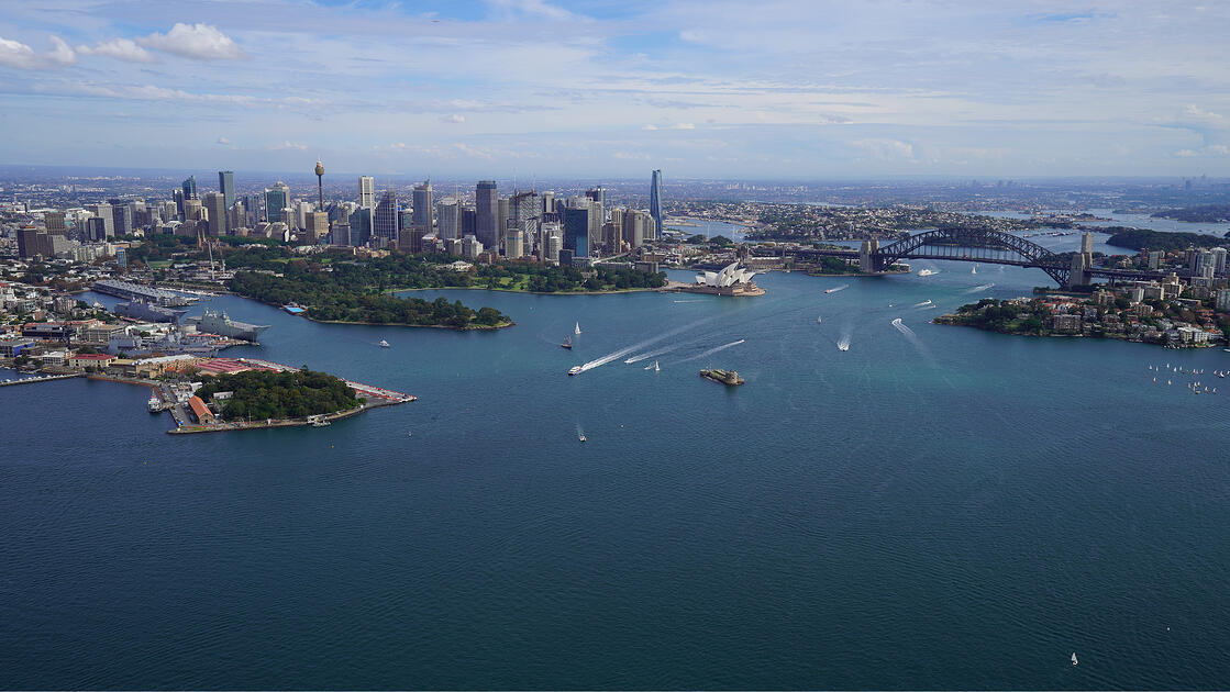 Aerial view of Sydney harbour with the city skyline in the background.
