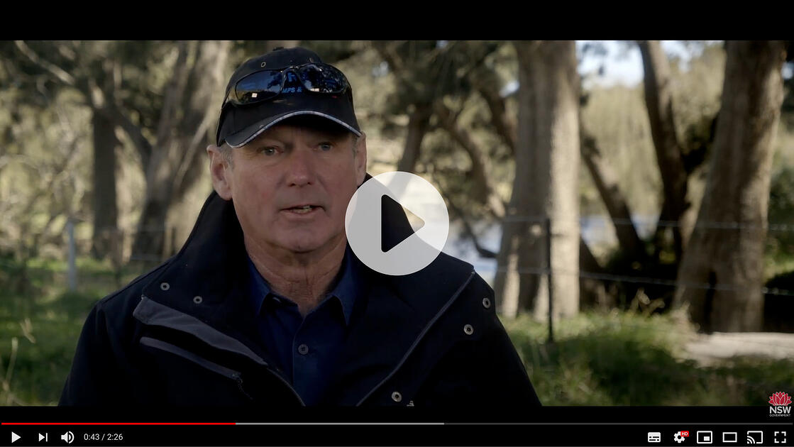 Video still of a man in a black jacket and baseball hat in an rural setting, speaking to the camera.